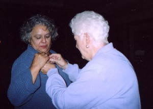 "President Kathryn ""Kitty"" Bates pinning ""Woman of Achievement"" pin on Marta Escañuelas"