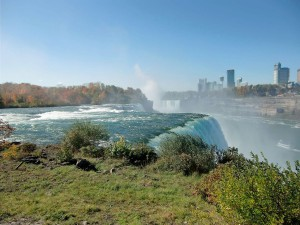 The Niagara River spills over the American Falls with the skyline of the city of Niagara Falls, Canada in the background.