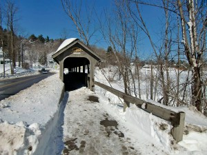 A small covered bridge leads out into the snow-covered hills.