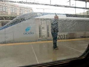 Through a rain-spattered window we see a sleek Acela train, Amtrak's fastest.