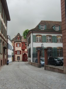 Not far from the Basel Munster are cobblestone streets and two and three story buildings with peaked roofs.