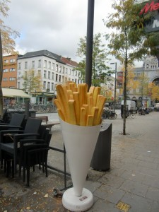 """A frites (French fry) shop features a huge cone outside with gigantic French fries protruding from it."""