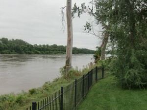 """We walk in a nearby park that looks out on the fast- flowing Missouri River, gray under an overcast sky."""
