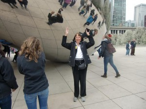Dolores stands by the Cloud Gate with her distorted image seen above and to the left.