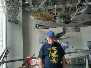 The author standing on a high deck of the museum with the B-17 bomber like he flew in during war suspended behind him.