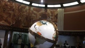 The rotunda af the L.A. Times building features a large globe of the world and sepia paintings around the walls.