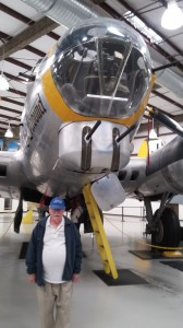 The author poses by the B-17, the type of plane in which he was the bombardier.
