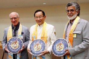Dr. Hong, Tao-Tze, president of the Federation of World Peace and Love, center, presents the compass clock of conscience to Bahrain's Cabinet Affairs Minister Mohammed Bin Ibrahim Al Mutawa, left, and Shaikh Hussam bin Essa Al Khalifa, president of Prince Khalifa bin Salman Al Khalifa Sustainable Development Award Committee, right, during the World Leader Summit of Love and Peace, at U.N. headquarters on Sept. 27, 2019. (AP Images)