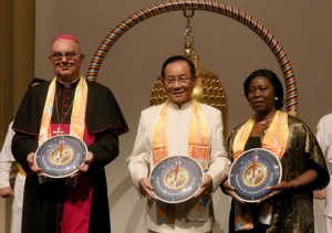 Bishop Camillo Ballin, left, and Ambassador Youngor Telewoda of Liberia to Austria, right, are each presented with a compass clock of conscience by Dr. Hong, Tao-Tze, president of FOWPAL. (AP Images)
