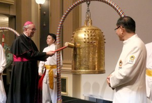 Bishop Camillo Ballin, Apostolic Vicar of Northern Arabia, left, rings the Bell of World Peace and Love. (AP Images)
