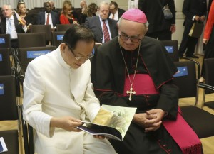 """Dr. Hong, Tao-Tze, president of FOWPAL, left, shares a book with Bishop Camillo Ballin, Apostolic Vicar of Northern Arabia. The book, titled """"Be the Spark,"""" serves as a fine tool for conscience education. (AP Images)"""